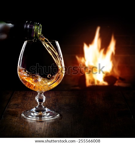 Bottle and glass of cognac over dark background with flame  - stock photo