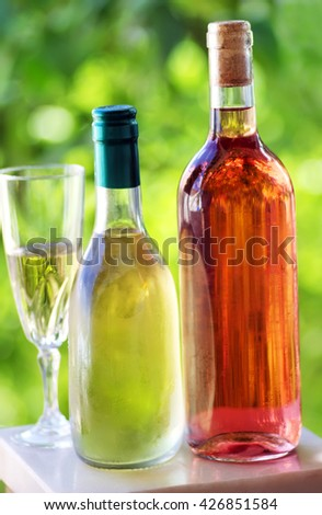 Bottle and glass of green and rose wine - stock photo