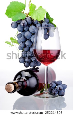 Bottle and glass of red wine, bunch of grapes with leaves isolated on a white background