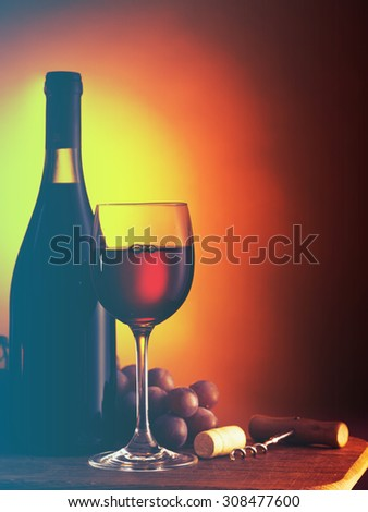 Bottle and glass of red wine on dark red background.Filtered image: cool cross processed vintage effect. - stock photo