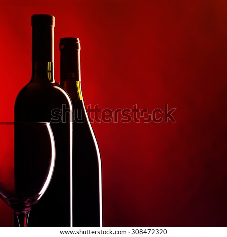 Bottle and glass of red wine on dark red background. Filtered image: vintage effect. - stock photo
