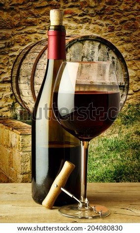 bottle and glass of red wine on the farm - stock photo
