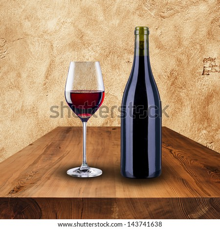 Bottle and glass of red wine on wood table and grunge wall - stock photo