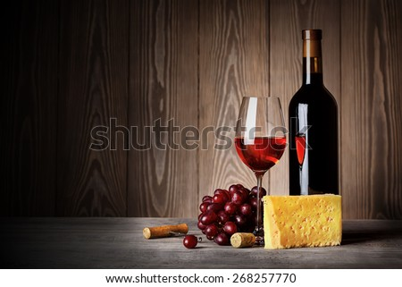 Bottle and glass of red wine with cheese grapes and corkscrew on wooden background - stock photo
