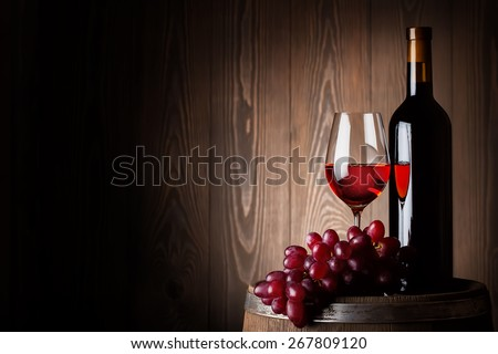 Bottle and glass of red wine with grapes on wooden barrel - stock photo