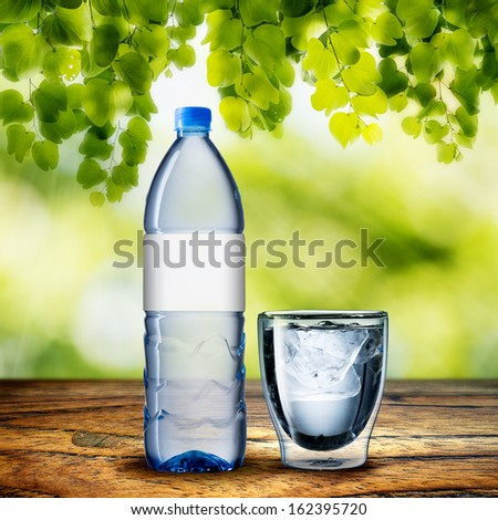 Bottle and Glass of Water on wood table and summer scene background - stock photo