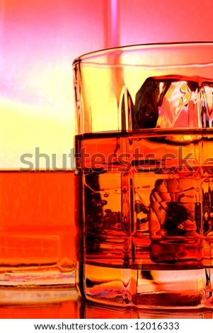 Bottle and glass of whiskey against multi colored abstract background. - stock photo