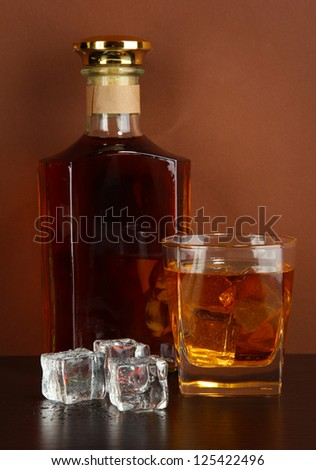 Bottle and Glass of whiskey and ice on brown background