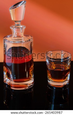 bottle and glass of whiskey on gradient background