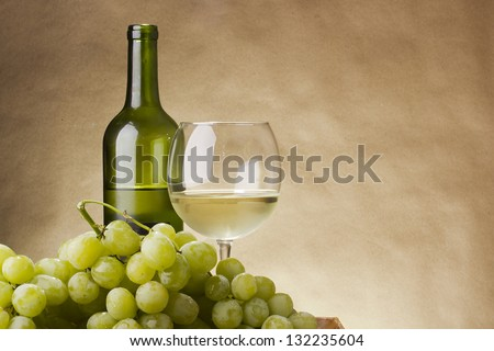 Bottle and glass of white wine and a bunch of grapes. - stock photo