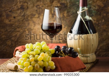 Bottle and glass of wine, bunches of grapes. - stock photo