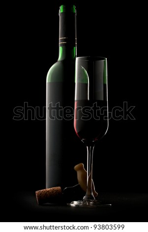 Bottle and glass of wine in black - stock photo