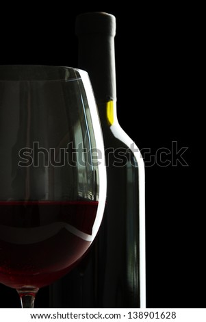 Bottle and glass of wine isolated on black - stock photo