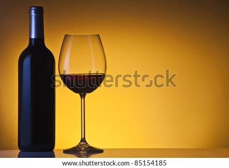 Bottle and glass of wine over orange bakground - stock photo