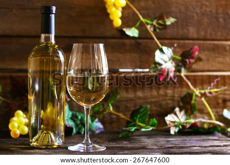 Bottle and glass of wine with grape on wooden background - stock photo
