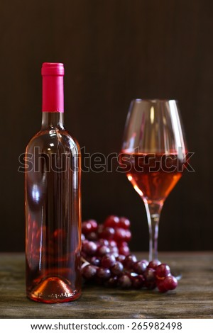 Bottle and glass of wine with grape on wooden table on dark background - stock photo