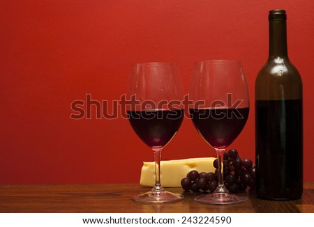 Bottle and glass of wine with red grapes and cheese