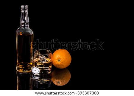 Bottle and glass whiskey with ice and wrist watch on black background - stock photo
