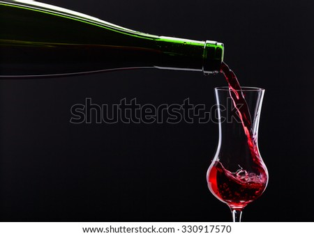 bottle and glass with alcoholic drink on black background - stock photo