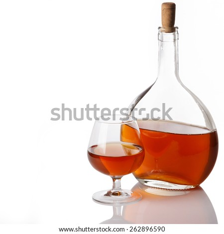 Bottle and glass with cognac on white background - stock photo