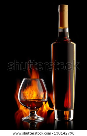 Bottle and glass with cognac over dark background with flame - stock photo