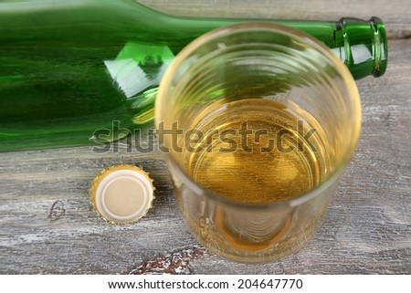 Bottle and glass with cold drink, on wooden background
