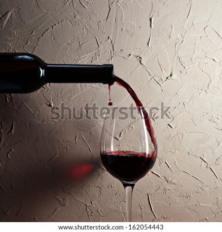 bottle and glass with red wine on a background of old wall