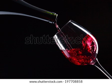 bottle and glass with red wine on  black background - stock photo