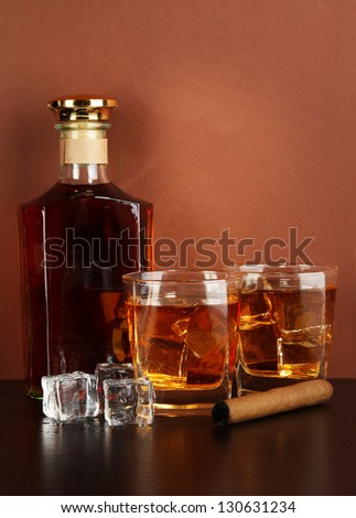 Bottle and Glasses of whiskey and cigar on brown background - stock photo