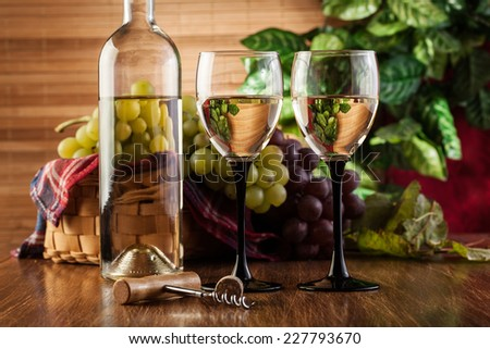 Bottle and glasses of white wine and bunches of grapes - stock photo
