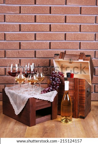 Bottle and glasses of wine and ripe grapes on table on brick wall background