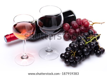 Bottle and glasses of wine with red and black grapes, isolated on white