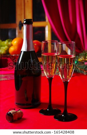 Bottle and two glasses of champagne on the red table