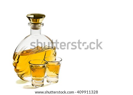 Bottle and two shot glasses of tequila on a white background - stock photo