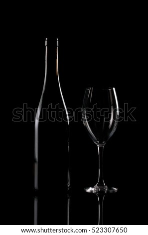 Bottle and wineglass on black background