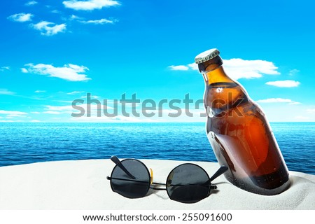 Bottle beer and sunglasses in the sand of a tropical beach - stock photo