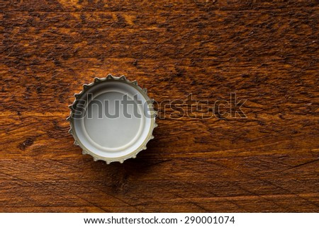 bottle cap from a beer bottle on wooden background - stock photo