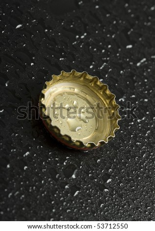 bottle cap with water droplets close up on black wet table background  - stock photo