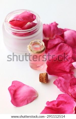 bottle essential oil rose fragrance pink petals cream container organic aroma cosmetic products - stock photo