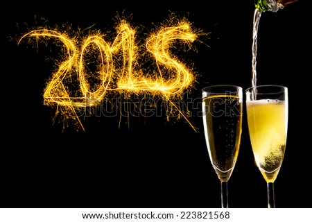 Bottle filling Champagne Glasses for celebrating new years eve 2015 with sparkling lightning numbers isolated on black background as new year greeting card - stock photo