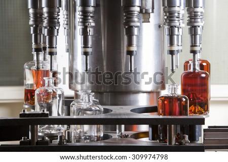 Bottle filling machine filling the bottles with liquor - stock photo