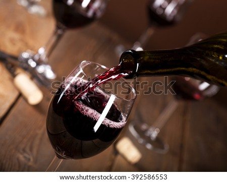 Bottle filling the glass of wine on wooden background
