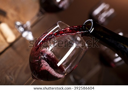 Bottle filling the glass of wine on wooden background - stock photo