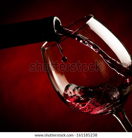 Bottle filling the glass of wine - splash of delicious flavor. - stock photo