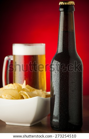 bottle, glass of beer and potato chips on stone table over red background - stock photo