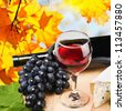 bottle, glass of red wine and assorted cheeses on a background of autumn leaves - stock photo