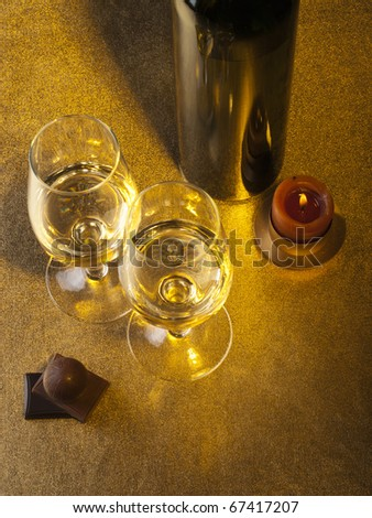 Bottle, glass with wine and candle on a gold  background