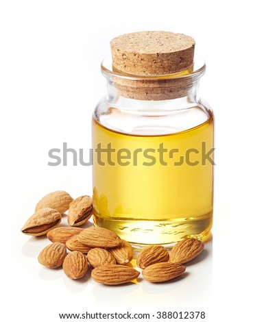 Bottle of almond oil and almonds isolated on white background - stock photo