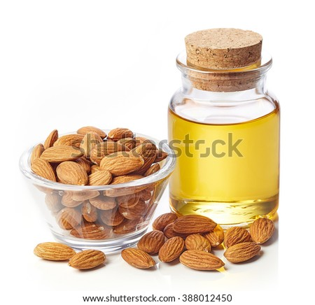 Bottle of almond oil and bowl of almonds isolated on white background - stock photo