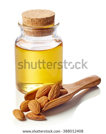Bottle of almond oil and wooden scoop of almonds isolated on white background - stock photo